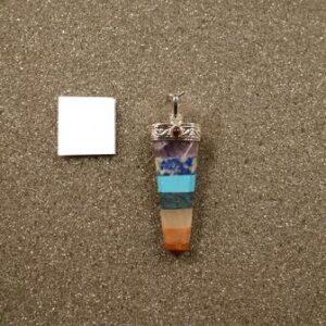 Ciondolo in 7 pietre differenti, cabochon in granato, montatura metallica. Dall'alto: ametista, lapislazzuli, pasta di turchese, diaspro, quarzo rosa, eosite e diaspro rosso. gr 5